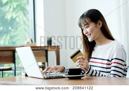 Young asian woman holding credit card and using laptop computer to shopping on line at cafe business and technology concept digital marketing casual lifestyle