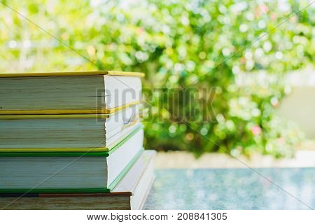 Stack of book on blurred natural background