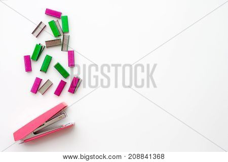 Top view of office accessories pink stapler and colorful of staples with space for your design image or text