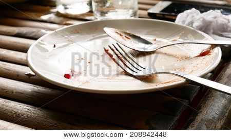 Plate with crumbs and used fork on wood background