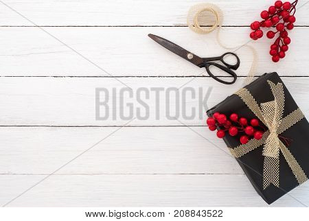 Gift wrapping. Hand crafted Christmas present gift box and tools on white wooden background. Flat layout top view composition copy space design.