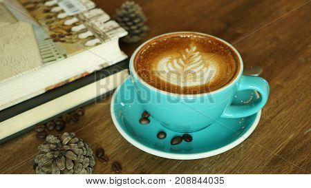 Hot coffee with textbook latte mocha espresso cappuccino with heart shape foam in green cup coffee shop wooden tabvle and coffee bean