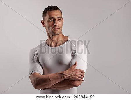 Portrait of fit healthy man posing on light gray background
