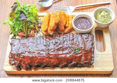 BBQ Ribs with potato and salad on wood plate