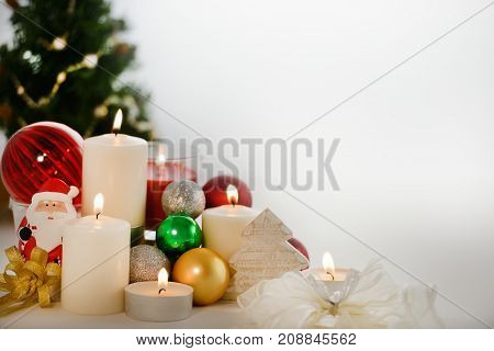 Festive Christmas decorations with candles ornaments and Chirstmas tree with copyspace on white