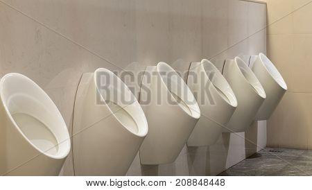 White urinals ceramic men's bathroom in business building