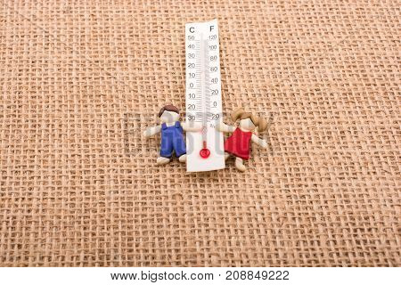 Thermometer Between A Boy And A Girl Figurine
