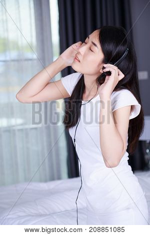 Woman In Headphones Listening To Music From Smartphone In Bedroom
