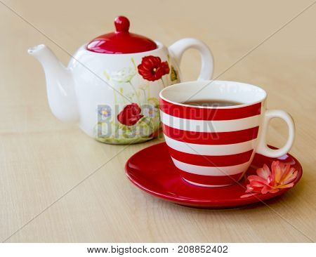 Striped Cup With Tea On A Saucer And Brewer With A Poppy Picture On A Wooden Table Top And Red Rose
