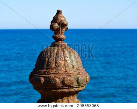 Decorative artistic metal pole covered with rust with clear blue sea ocean background