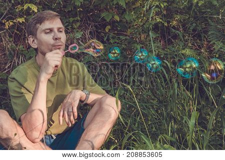 Young Man Blowing Soap Bubbles. Man In Summer Forest In The Mountains.