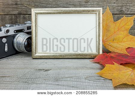 Retro Camera And Photo Frame On Wooden Background With Colorful Fallen Leaves