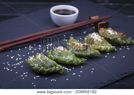 Ukrainian and Russian dishes - green vareniki or dumplings with beef meat or mashed potatoes or cottage cheese in the dough together with spirulina on a black slate background close up