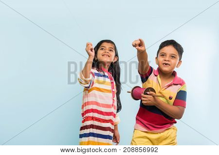 Kite or Patang flying in India, two cute little indian kids enjoying Kite flying in Makar sankranti festival, standing with chakri or wooden spindal and holding thread in excitement on blue background