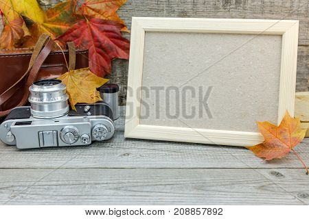 Empty Photo Frame, Retro Camera On Old Grey Wooden Desk With Vibrant Fallen Leaves