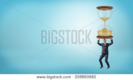 A businessman holds a large heavy hourglass in his hands on blue background. Winning over time. Wise schedule making. Career and planning.