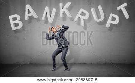A scared businessman hides under large concrete letters making a word Bankrupt above him on a grey background. Business and loss. Financial trouble. Losing all earnings.