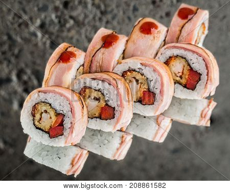 Roll with bacon, fried shrimp and paprica over concrete background