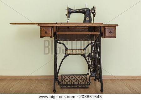 BacauRomania - May 16 2011: Image of the old Singer Sewing machine in a empty room with parquet. Issac Singer built the first sewing machine with vertical needle movement powered by foot treadle.