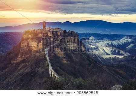 Medieval italian landscape. Ancient mountain village. Civita di Bagnoregio, Italy. A long bridge to reach the village. Mountain range in the background. Sunset.