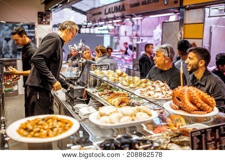 BARCELONA, SPAIN - August 16, 2017: Restaurant full of people in La Boqueria market one of the most popular tourist landmarks in the Ciudad Vieja district in Barcelona