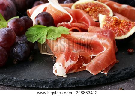 prosciutto with parsley figs and grapes on a black stone food tray.