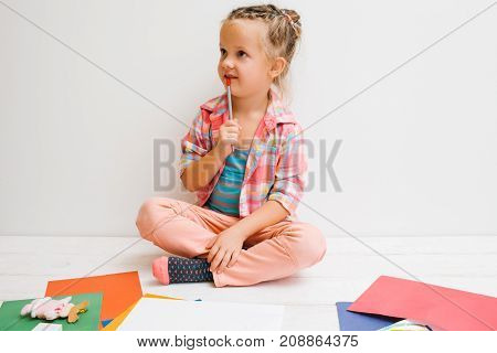 Many ideas for art. Thoughtful process. Small artist girl on white background, invent interesting painting. Dreaming child, thought concept