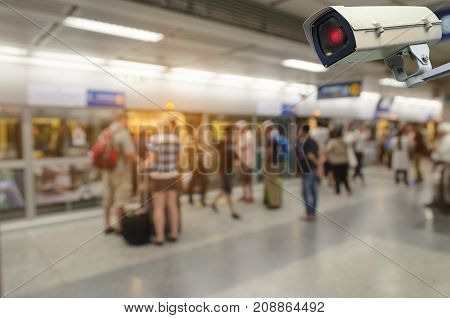 CCTV security camera system operating with people waiting subway at train station surveillance security and safety technology concept