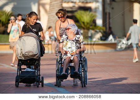 PORTO AZZURRO, ITALY. June 26, 2016: Disabled with wheelchair. Woman with pram. A woman pushes a wheelchair with a child inside. A woman pushing the wheelchair with his mother over.