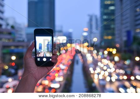 Close up Woman hand taking photo with smart phone on the traffic jam and buildings with traffic night light background in the city. Copy space.