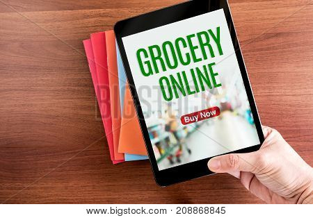 Top View Of Hand Holding Tablet With Grocery Online Word With Icon Over Color Notebook On Wooden Tab