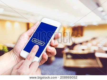 Hand Holding Mobile  With Order Button And Empty Screen For Adding Your Design At Blur Seminar Meeti