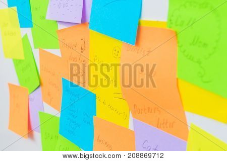 To do list - multicolored task notes close up on white wall
