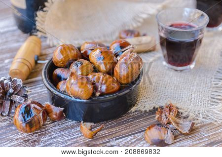 Tasty roasted chestnuts on ceramic bowl served with red wine on wooden rustic table. Festive winter holiday treats background.