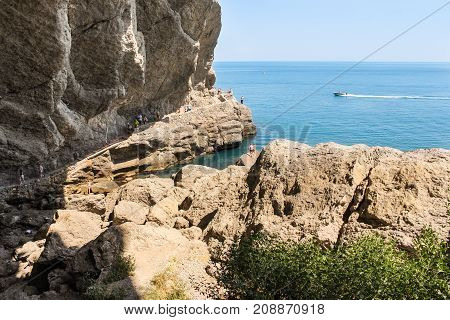 New World, Crimea - 12 July, People under the rock by the sea, 12 July, 2017. Travel along the coast along the path of Prince Golitsyn.