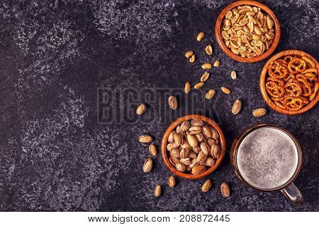 Beer, Nuts And Pretzel On Stone Background.