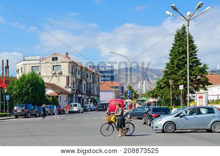 SHKODER ALBANIA - SEPTEMBER 6 2017: Street (Rruga Vilson) Grand Hotel Europa in city center of Shkoder Albania. Unknown people ride bicycles and walk down street