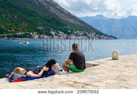 PERAST MONTENEGRO - SEPTEMBER 10 2017: Unknown tourists rest on Island of Virgin on reef (Gospa od Skrpela Island) in Bay of Kotor Montenegro