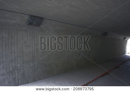 Concrete tunnel with light comming in at the end