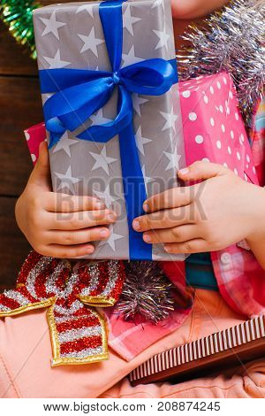Happy New Year day. Christmas miracle. Everything for little kid, many presents for unrecognizable child closeup. Joyful mood, festive concept