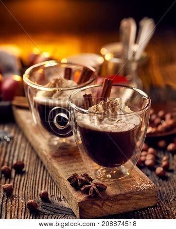 Hot chocolate with whipped cream, sprinkled with aromatic cinnamon in glass cups, on a rustic wooden table. Delicious and warming drink.
