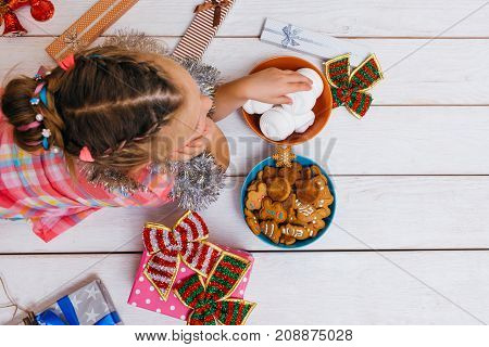 Dream life on Christmas. Satiated child. Thoughtful baby girl on white background with free space. Good choice of sweets top view, festive mood on New Year