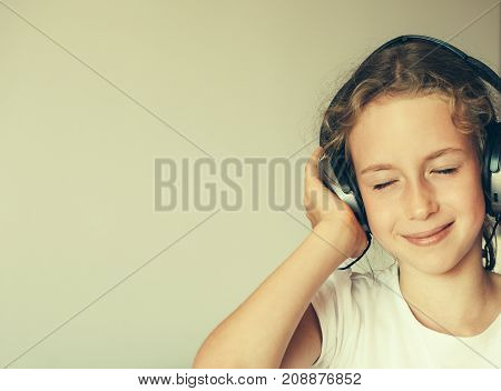 Little girl listening to the music in headphones.