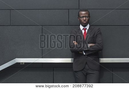 Outdoor Image Of African American Businessman Pictured Against Grey Background Dressed In Formal Sui