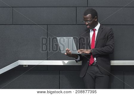 Urban Portrait Of Young Dark-skinned Entrepreneur Standing In City Center With Grey Wall Behind Chec