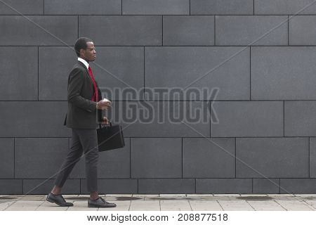 Horizontal Shot Of Young Dark-skinned Businessman Spending Time From Work Walking In City Center In
