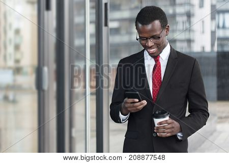 Indoor Portrait Of Busy African Chief Executive Officer Pictured In Afternoon, Holding Smartphone In