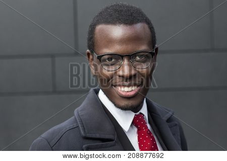 Horizontal Headshot Of Dark-skinned African Entrepreneur Pictured Against Gray Wall Wearing Formal C