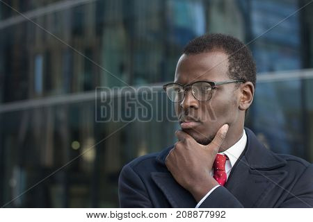 Horizontal Headshot Of Attentive African American Executive Standing Outdoors, Casting Side Look Thr