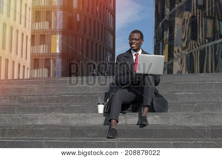 Horizontal Image Of Handsome Dark-skinned Man Wearing Formal Clothes And Glasses Using Laptop While